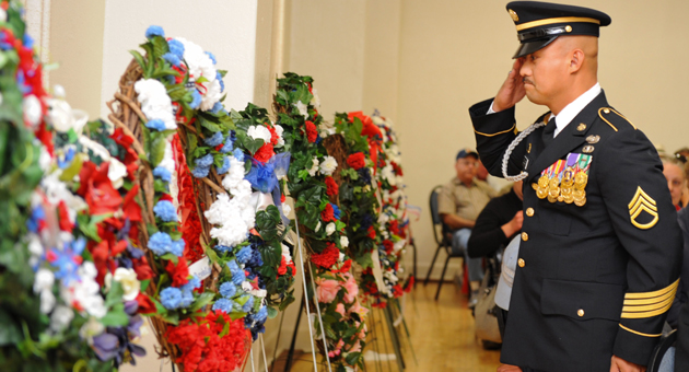 Staff Sgt. Ronald Zulueta, who was awarded a Purple Heart medal on Monday from Rep. Lois Capps, D-Santa Barbara, salutes an honorary wreath during the Memorial Day ceremony at the Veterans Memorial Building in Santa Barbara.