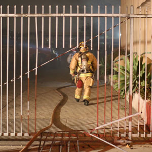 Santa Barbara firefighters had to cut through a metal gate to gain access to a fire at a Lower Eastside business early Saturday on Calle Cesar Chavez. (Urban Hikers photo)