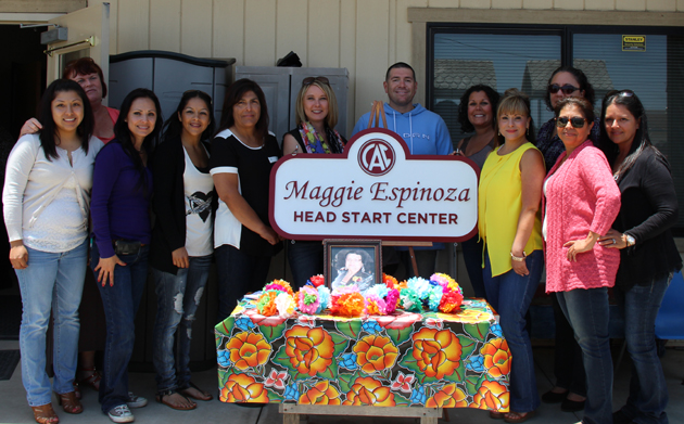 <p>Community Action Commission staff gather around the sign for the newly dedicated Maggie Espinoza Center.</p>