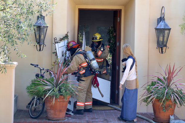 Firefighters mop up Sunday after a fire broke out at a Montecito home. Officials say fire sprinklers in the residence kept the flames in check.