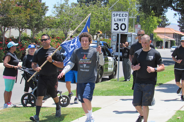 "With members of the Santa Maria Police Department by his side, Special Olympian Mattie Luna carries the ""Flame of Hope"" as the Law Enforcement Torch Run for Special Olympics Southern Califoria continues its route in Santa Maria Tuesday."
