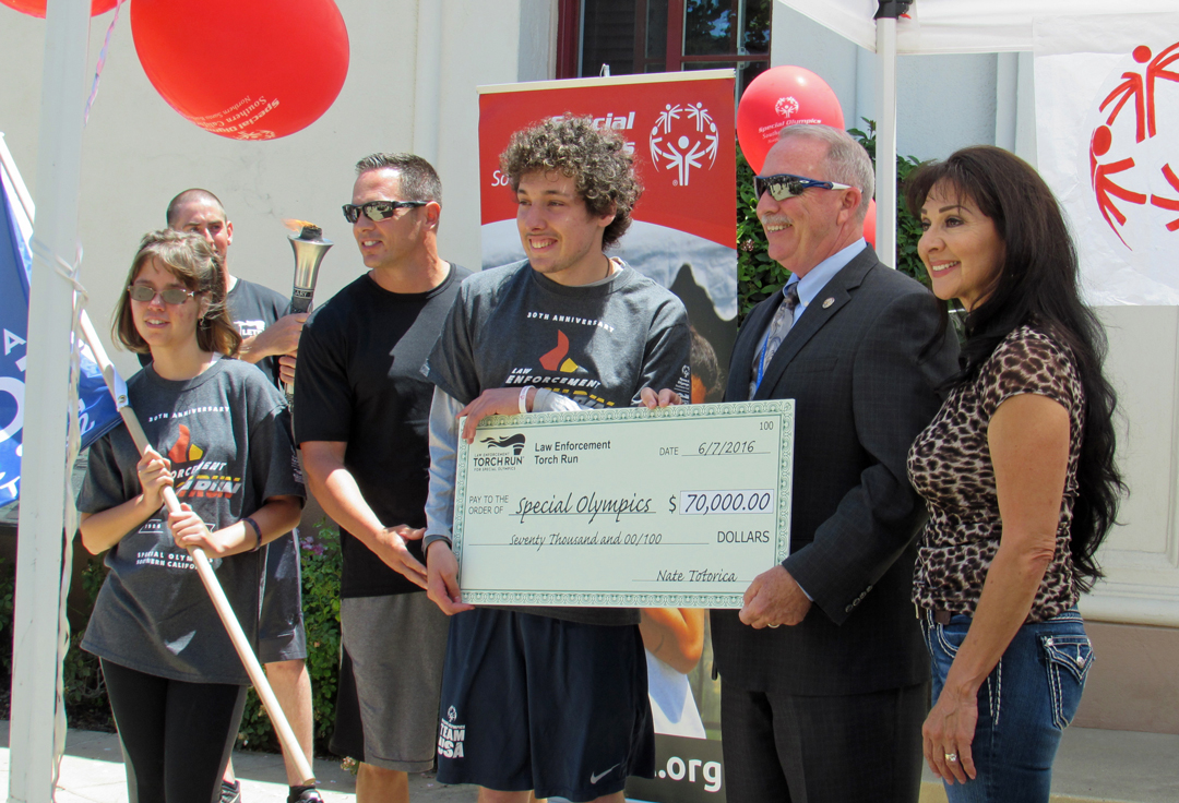 The Law Enforcement Torch Run presented $70,000 to Special Olympics on Tuesday. Pictured are Special Olympian Kaitlyn Luna, Santa Maria police detective Nathan Totorica, Special Olympian Mattie Luna, police Chief Ralph Martin and Mayor Pro-Tem Etta Waterfield.