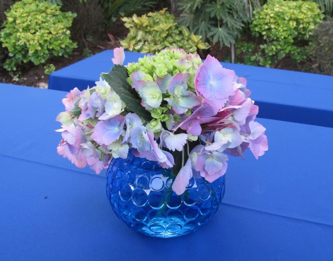 A hydrangea centerpiece complements the event's blue color scheme.