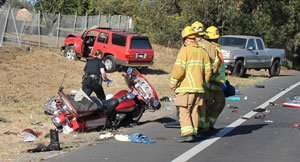 Santa Barbara police and firefighters investigate the wreckage of a May 29 motorcycle crash on Old Coast Highway near Montecito Country Club. A Canadian couple was critically injured when they were struck by a motorist allegedly driving under the influence, but the quick response of two passers-by is credited with saving their lives. (Urban Hikers photo)