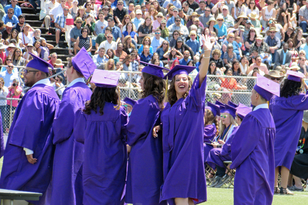 A Righetti High School graduate waves to well-wishers while waiting in line to get her diploma Thursday.