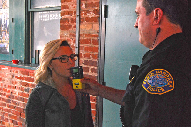 A bar patron takes a voluntary breathalyzer test offered by Santa Barbara police officers as part of the Know Your Limits campaign aimed at reducing drunken driving.