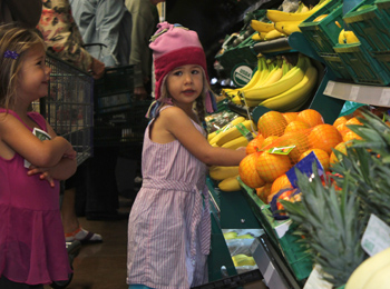 Three-year-old sisters Natalie, left, and Lila Warren, shopping with dad Mark, check out the produce section at Fresh & Easy Neighborhood Market.