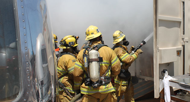<p>Santa Barbara city firefighters spray water on a fire that was discovered Sunday in a storage container at an industrial site on Quarantina Street.</p>