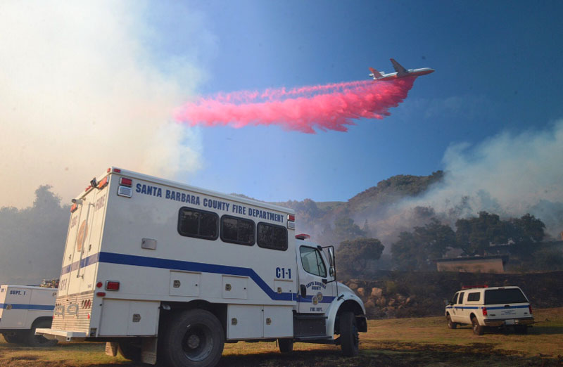 A giant DC-10 air tanker drops a load of retardant on the vegetation fire burning in Refugio Canyon.
