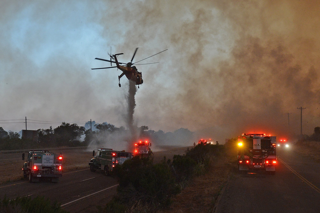 A skycrane helicopter makes a drop on the Highway 101 center divider at El Capitan State Park.