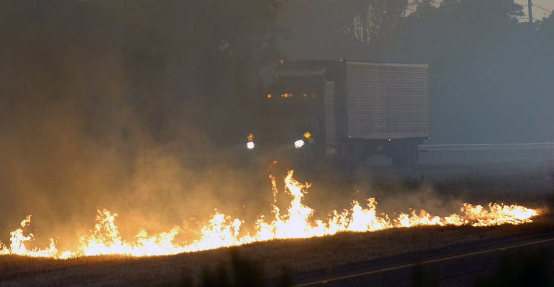 A tractor-trailer drives by a fire in the center median of Highway 101 near El Capitan State Park Thursday night.