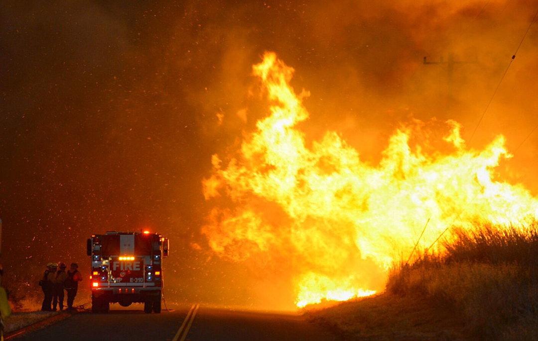 Firefighters take shelter behind the engine as flames advance near El Capitan State Beach Thursday night.