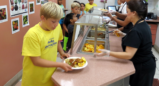 <p>Students enjoy a free meal of orange chicken and sesame noodles with orange slices on Tuesday at Monroe Elementary School through the Santa Barbara Unified School District&#8217;s Summer Food Service Program.</p>