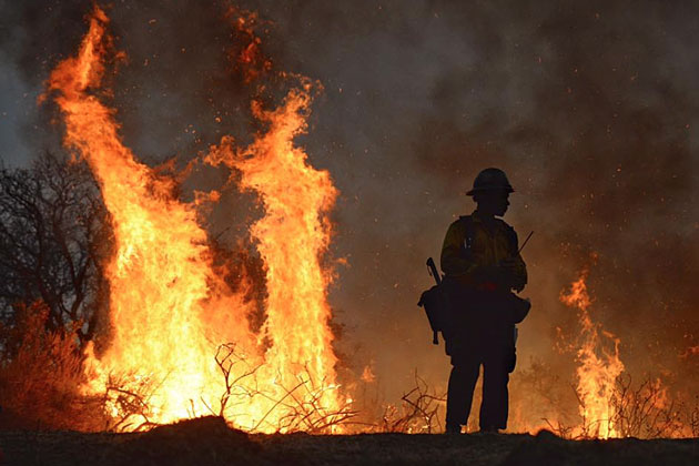 A firefighter watches flames from the Sherpa Fire.