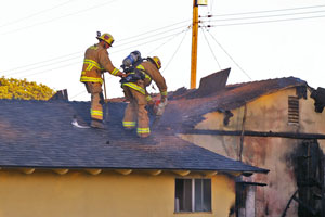 Firefighters use a chainsaw to cut ventilation holes in the roof of a home that burned Tuesday on Momouth Avenue in Goleta. (Tom Bolton / Noozhawk photo)