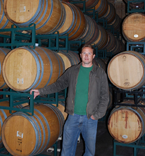 Ryan Carr, standing next to wine barrels at Carr Vineyards and Winery, manages more than a dozen vineyards.