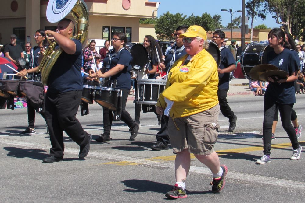 Lompoc Valley Flower Festival Parade volunteer Kelly Murphy marches alongside the South East High School band Saturday.