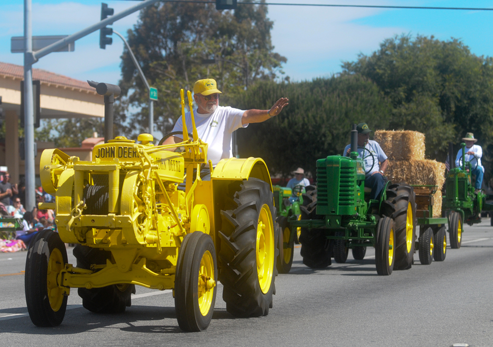 Members of the River Bottom Boys Antique Tractor Club wave to parade watchers.