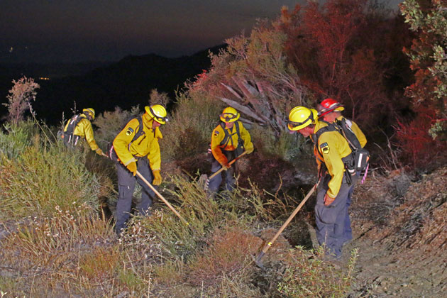 Firefighters mop up Tuesday night after a small vegetation fire broke out along Painted Cave Road in the mountains above Santa Barbara.