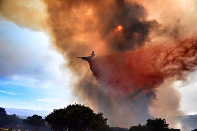 A bomber drops a load of fire retardant on the vegetation fire burning Monday in the Burton Mesa area near Lompoc. By the evening hours, the fast-moving blaze had calmed considerably, and was 55% contained, with full containment expected Tuesday.