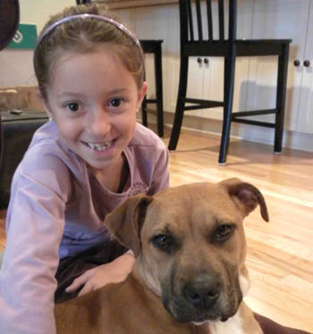 Seven-year-old Maya Lewandowski with her adopted dog, Lucy.