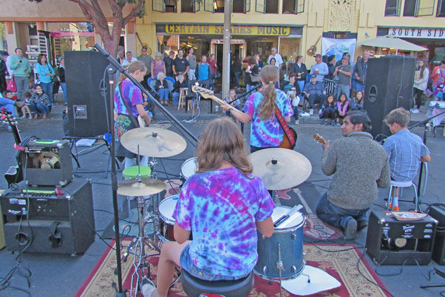 People pause to listen to The Same Difference perform during the Lompoc Old Town Market on Friday night.