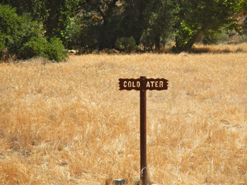 An iron sign to Coldwater Camp is posted in the dry meadow.