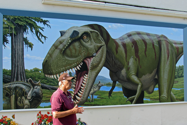 As a dinosaur appears poised to chomp his head, Lompoc Valley Chamber of Commerce CEO/President Ken Ostini talks about the city's newest mural.