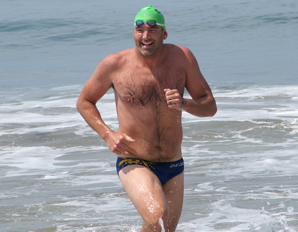 Tim Siciliano runs up the beach after finishing first in the Semana Nautica 6-mile swim from the Goleta Beach Pier to Hendry's Beach.