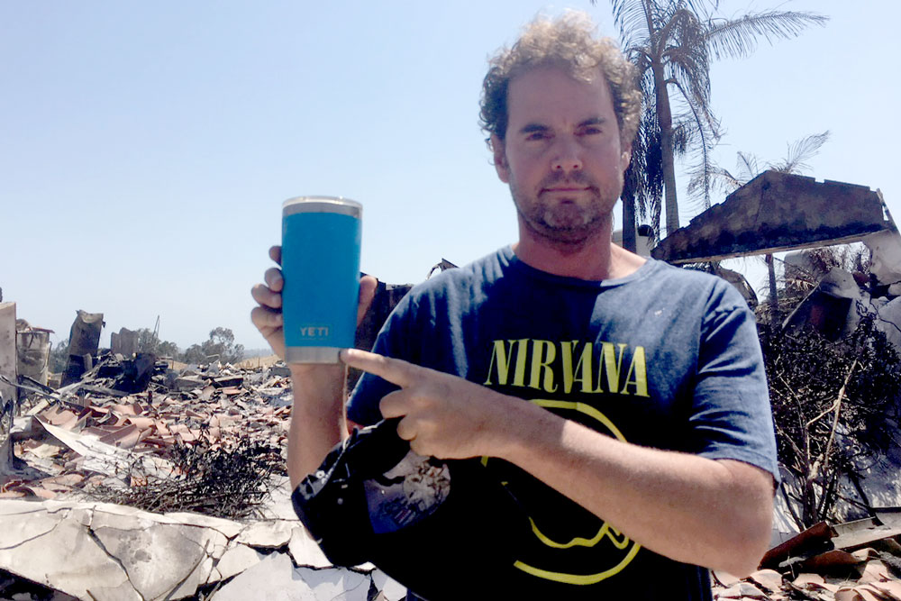 Man holding cup in front of home destroyed by fire.