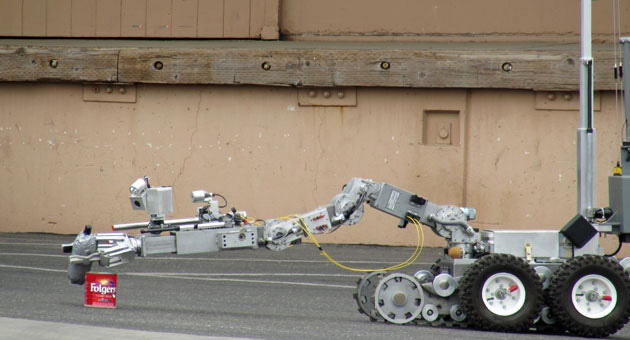 <p>A robot examines a suspicious device — a bottle wrapped in duct tape with what appeared to be a fuse — on Friday in Santa Maria. The robot later destroyed the device.</p>