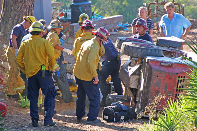 Emergency personnel prepare a 67-year-old man for transport to Santa Barbara Cottage Hospital on Saturday after the tractor he was driving rolled over down a hillside in Mission Canyon.
