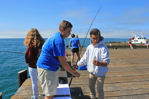 "Nicolas Hosking, left, helps his friend Alex Hernandez remove a mackerel from a fish hook Monday at Stearns Wharf. Both of them support the city's plan to enforce the ""No Fishing"" areas with signs in other areas of the wharf."