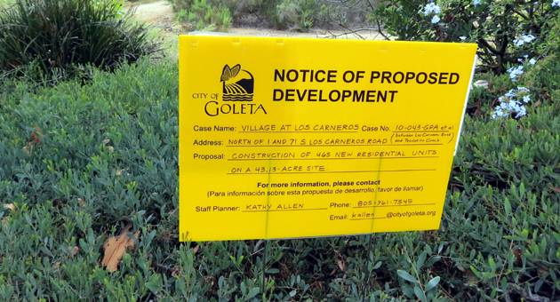 <p>A sign marks the proposed location of the Village at Los Carneros development. Residents have expressed concern with how close the 465-unit project would be to the nearby creek bed, pictured in the background.</p>
