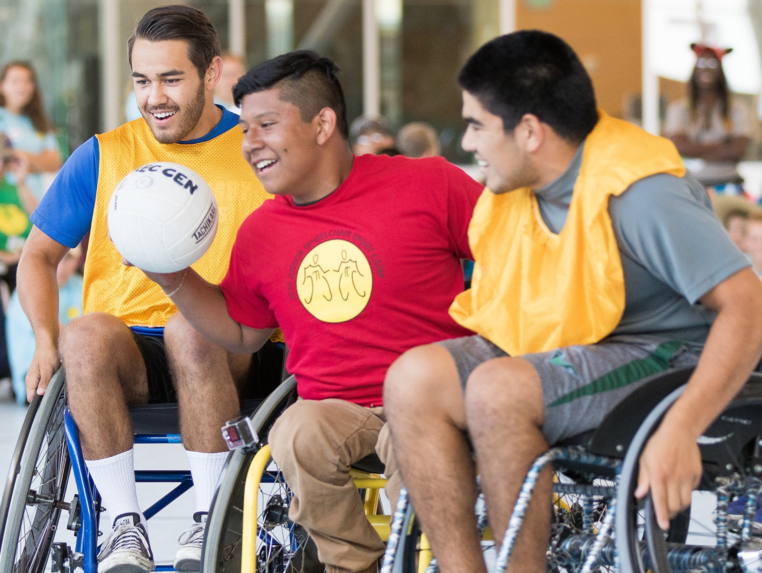 Jesus Alverado, center, of the Junior Wheelchair Camp team, and UCSB rugby players Anthony Singh, left, and David Cota are all smiles as they play in a wheelchair rugby game at the Rec Center.