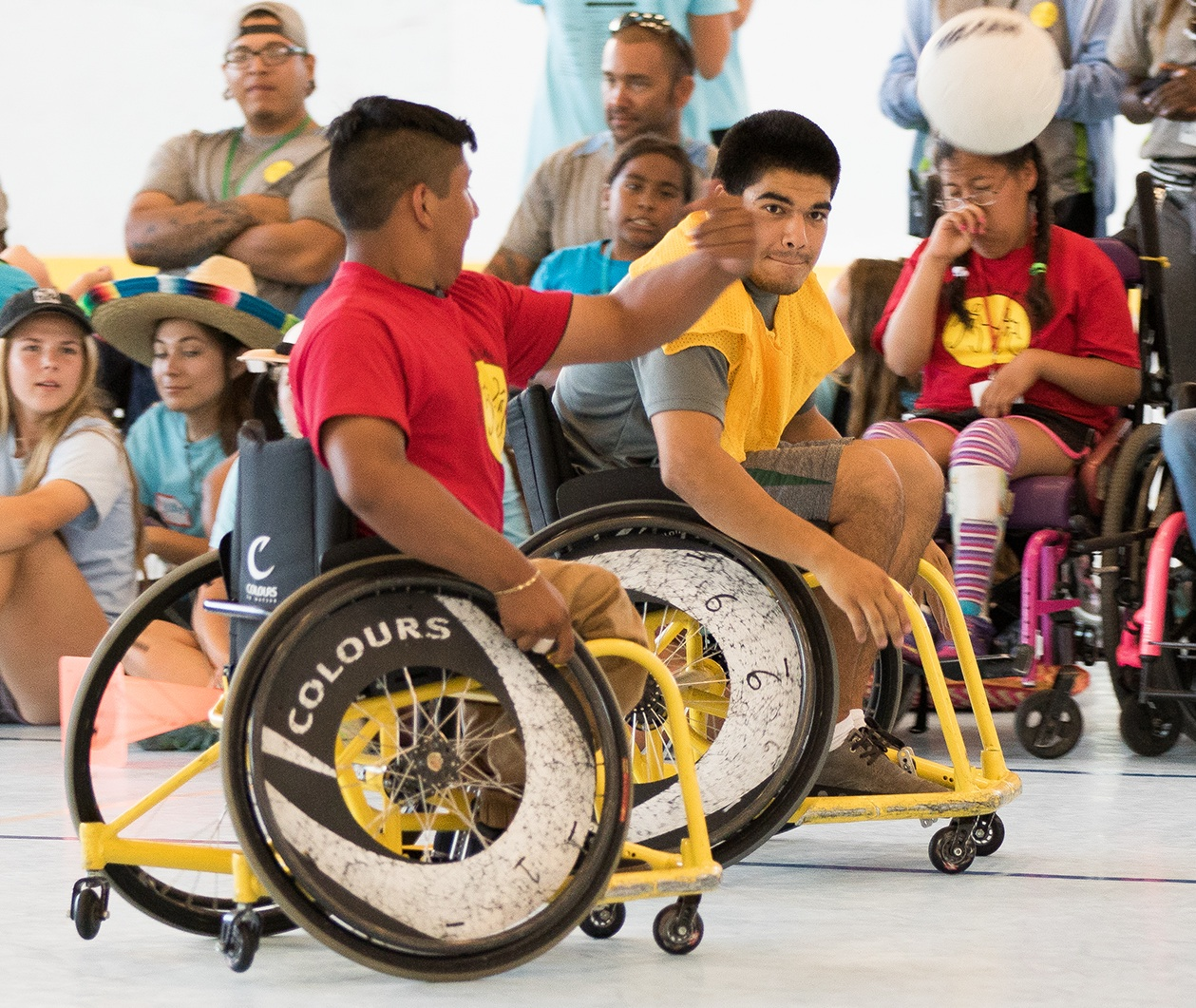 Jesus Alverado of the Junior Wheelchair Camp team throws a no-look pass while being chased by UCSB's David Cota.
