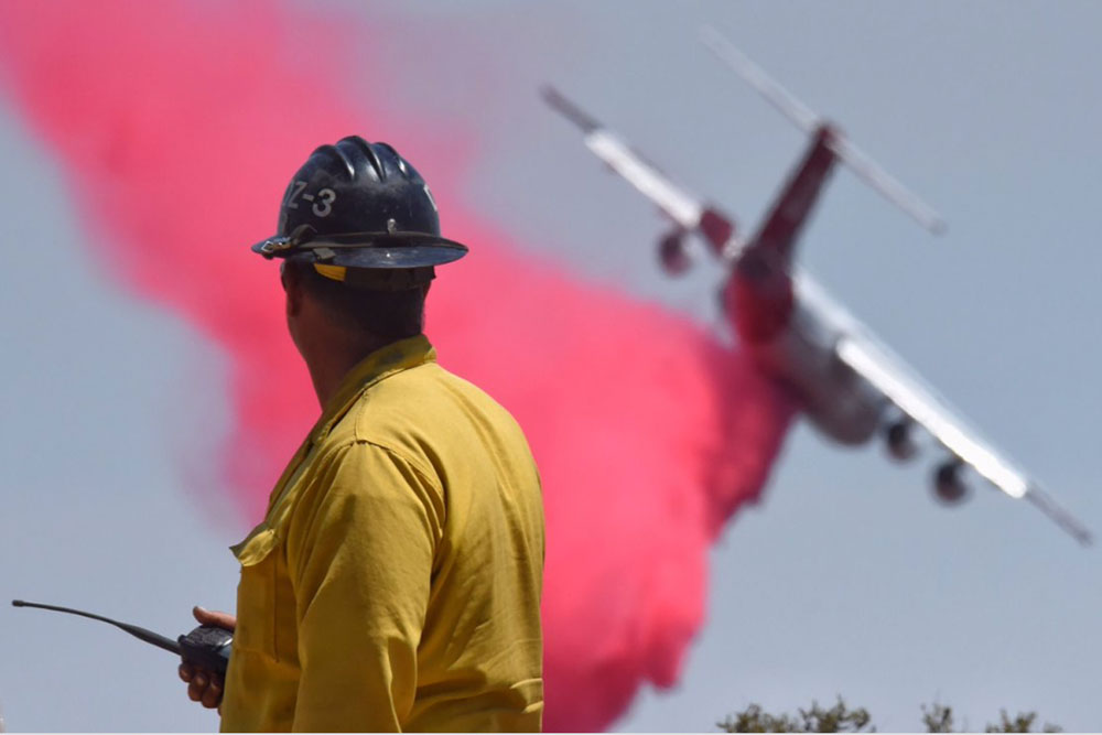 A firefighter watches as a BAe-146 makes a retardant drop along the western flank of the Whittier Fire near West Camino Cielo on Saturday.
