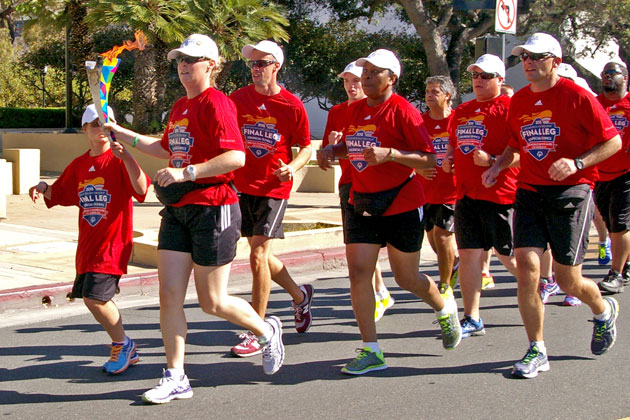 Runners participating in the Special Olympics Relay Across America carry the Flame of Hope down Anapamu Street on Friday on their way to the Santa Barbara County Courthouse.