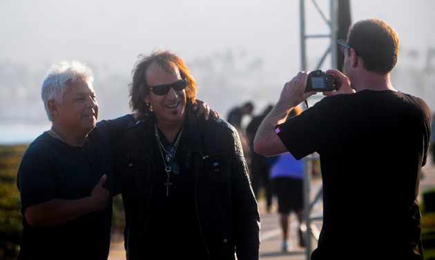 <p>Santa Barbara resident Ben Rios, left, gets his photo taken Thursday with REO Speedwagon guitarist Dave Amato at East Beach. The band was in town to perform for a private Citgo-hosted party at the beach.</p>