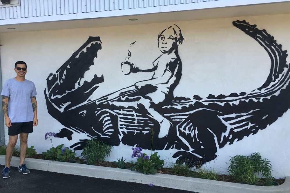 The Gatorboy mural that was rejected by the city of Santa Barbara adorns a wall of the new Cajun Kitchen location on Calle Real in Goleta. Pictured above is co-owner Juan Jimenez.