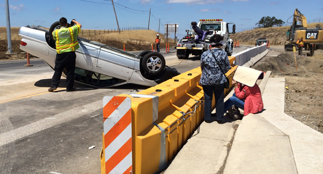 <p>Emergency crews respond Monday morning to the scene of a vehicle rollover in the partially completed roundabout at the intersection of Highways 154 and 246.</p>