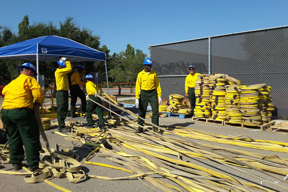 As the Whittier Fire winds down, crews are pulling hoses off the fire lines. A California Conservation Corps crew, above, rolls up hoses and prepares them for shipment back to the warehouse for use on other blazes.