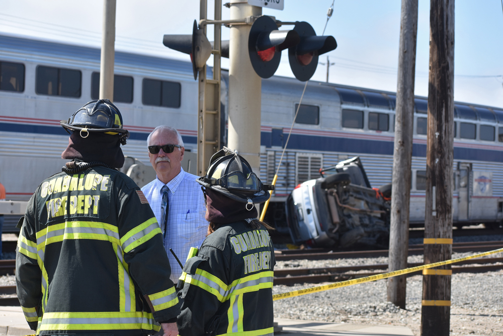 Guadalupe Public Safety Director Gary Hoving talks to city firefighters at the scene of a crash between a vehicle and an Amtrak train Monday afternoon.