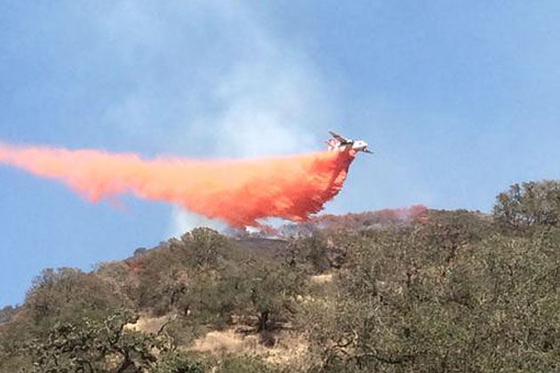 An air tanker drops a load of retardant on a fire burning Saturday afternoon in a rural area east of Santa Maria. The blaze charred 52 acres and was contained by Sunday night.