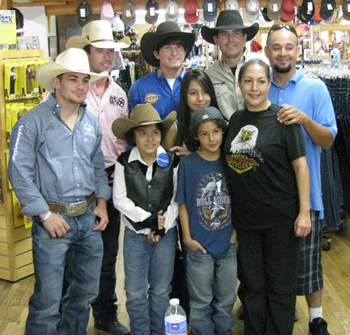 Damian Gomez, front left, and his family pose with members of the Professional Bull Riding Tour on Thursday at Jedlicka's Saddlery. (Giana Magnoli / Noozhawk photo)