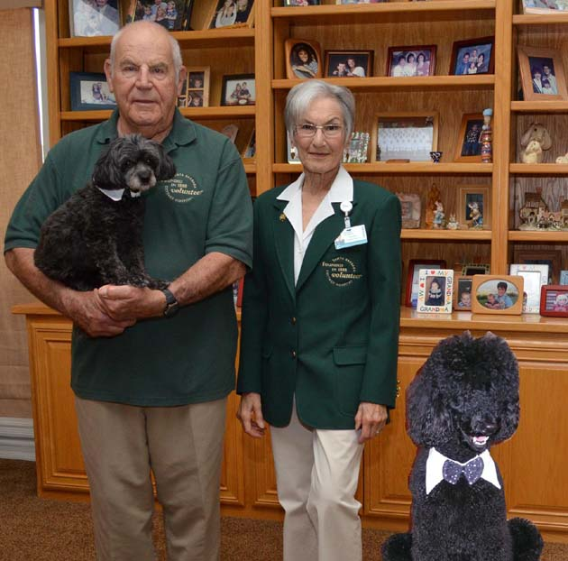 <p>Handlers Paul and Nadine Melancon and therapy dog Dr. Tessy, in Paul&#8217;s arms, are a welcome sight for patients at Santa Barbara Cottage Hospital.</p>