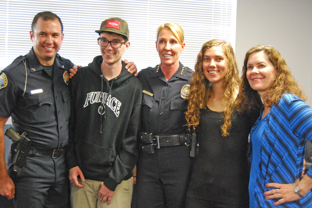Drew Daly, second from left, and his family dropped by the Santa Barbara police station on Thursday to offer their thanks for efforts to save his life after he was gravely injured by a hit-and-run driver in December. With him, from left, are Officer Ethan Ragsdale, Police Chief Lori Luhnow, his sister, Leah Daly, and his mother, Teresa Howe.