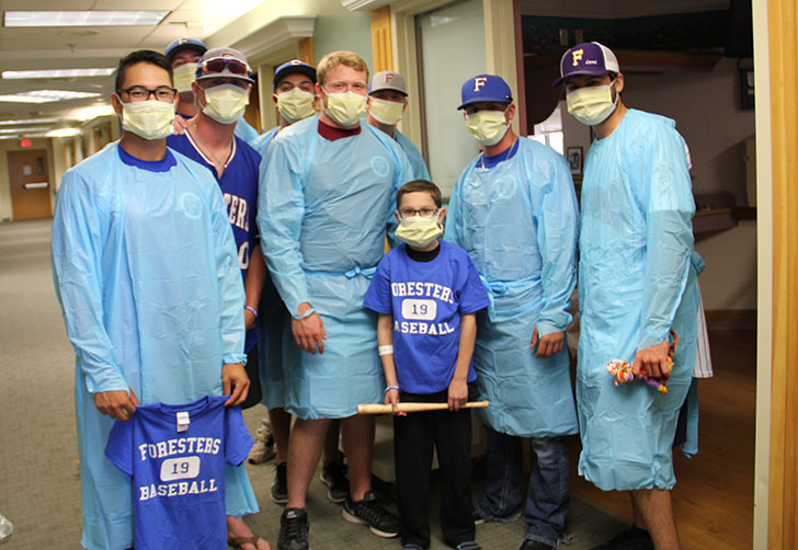 The 2016 Foresters wear hospital garb as they meet with a young man who met the 2006 team when it visited Via Christi Hospital as part of the club's Hugs for Cubs program to support young cancer patients.