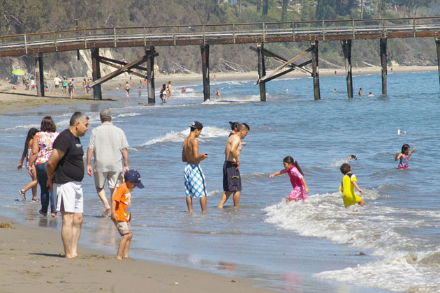 People flocked to the shoreline at Goleta Beach on Friday to beat the heat, which is expected to continue through the weekend.