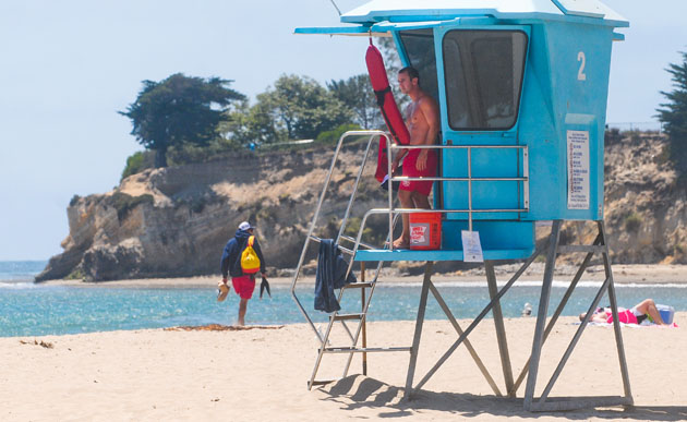 A Santa Barbara lifeguard keeps a close eye on the water just east of Leadbetter Point on Wednesday, the day after a surfer reported seeing a great white shark swimming 20 to 30 yards off the point. (Lara Cooper / Noozhawk photo)